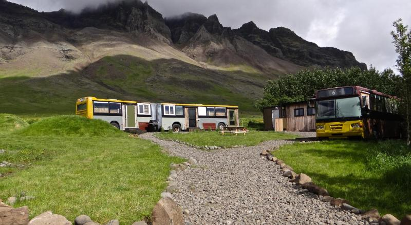 a unique hotel in Iceland - 2 buses in a campground with mountains in the background