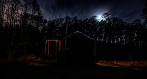 Ocieplona nowoczesna jurta z kominkiem White Shaman Yurt na drewnianym wysokim podeście